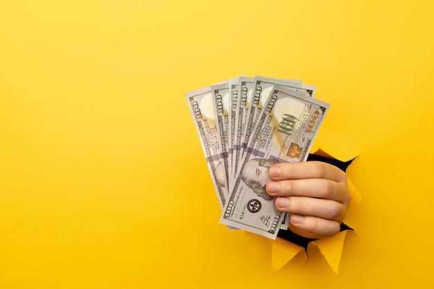 手にドル通貨。黄色い紙の穴からドル紙幣を持っている手。