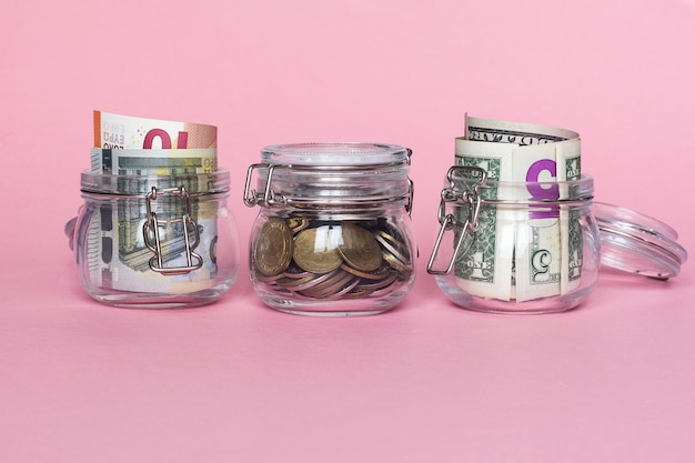 Dollar, euro and coins in glass jar on pink background. saving money concept