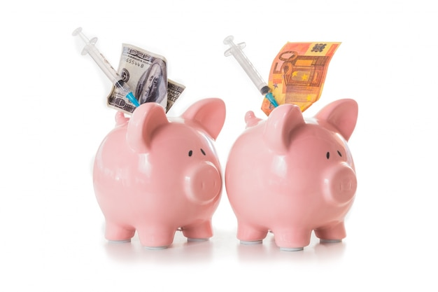 Dollar and euro notes and syringes sticking out of piggy banks