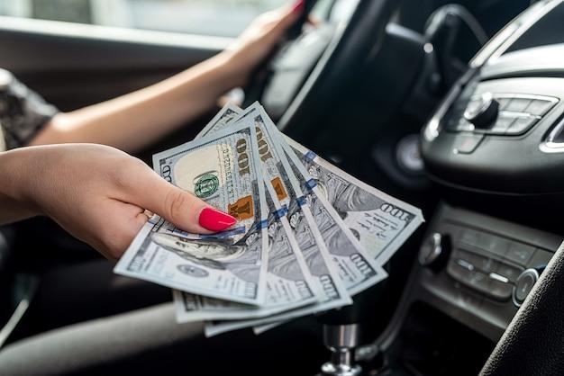 Dollar in female hand inside car, close up