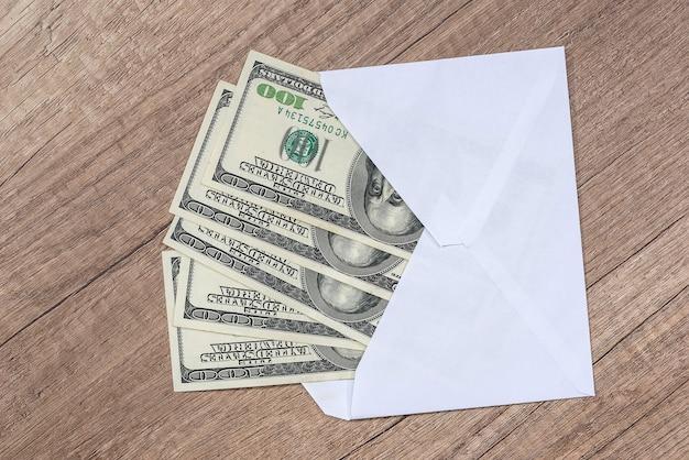 机の上の封筒のドル。貯蓄の概念。