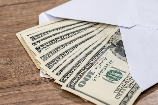 책상에 봉투에 달러입니다. 저축 개념.