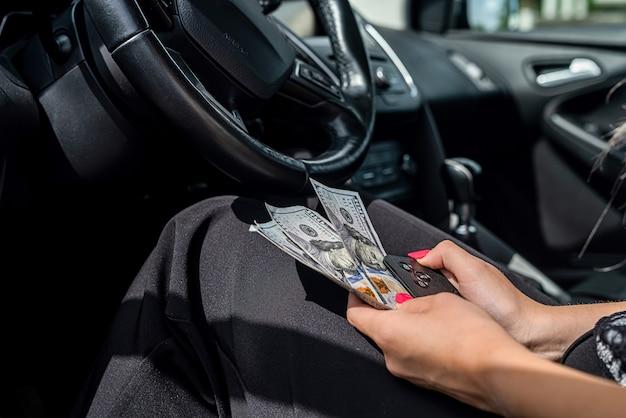 차 안에 여성의 손에 달러를 닫습니다