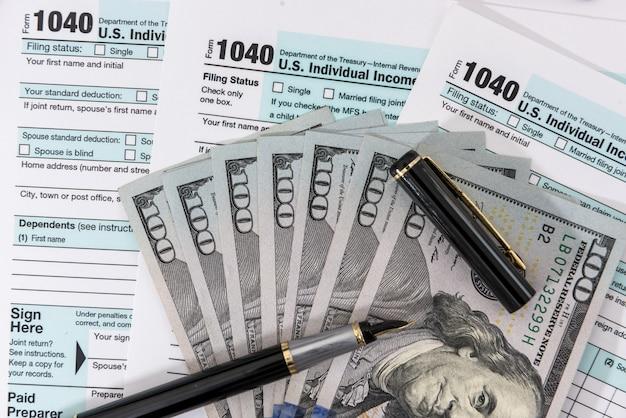 ペンで私たちの税務フォームに横たわっているドル。税の概念