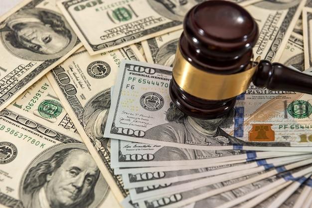 ドルのお金と裁判官のガベルがテーブルに。判断と賄賂。腐敗