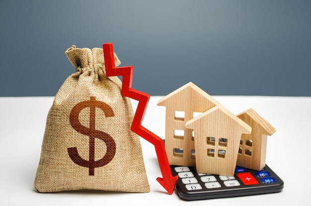 Мешок денег доллара с стрелкой вниз и домами на калькуляторе. падающий рынок недвижимости, низкие цены