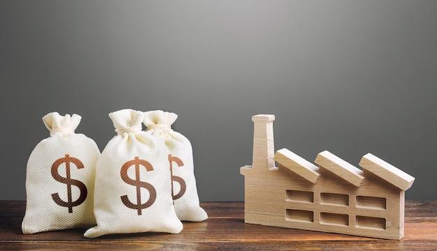 ドルのお金の袋と産業工場の工場