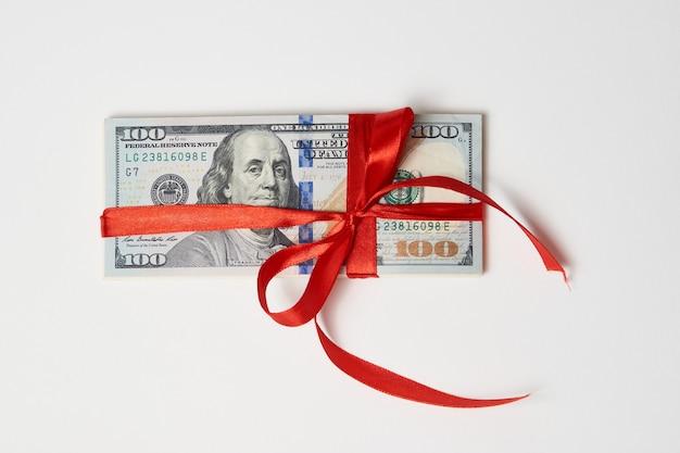 Долларовые деньги с красной лентой на белом фоне с копией пространства. денежный подарок