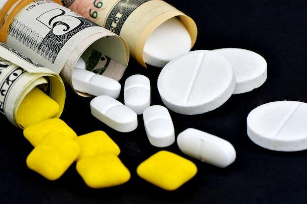 달러에 고립 된 검은 배경 밖으로 흐르는 환 약으로 올리고