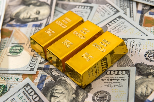 Доллар с золотыми слитками как концепция финансового богатства или сбережений. куча нас банкноты и золота. богатые деньги