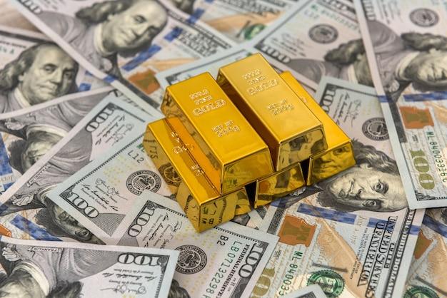 금융 부 또는 저축 개념으로 황금 막대와 달러. 우리 지폐와 금 더미. 돈이 부자