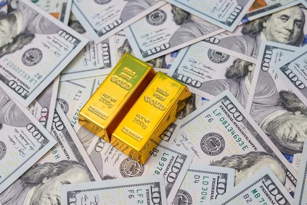 Доллар с золотыми слитками как концепция финансового богатства или сбережений. куча нас банкноты и золота.