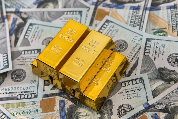 금융 부 또는 저축 개념으로 황금 막대가있는 달러