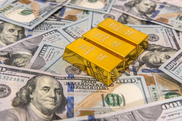 Dollar with golden bars as finance wealth or savings concept. pile of us banknote and gold. money rich