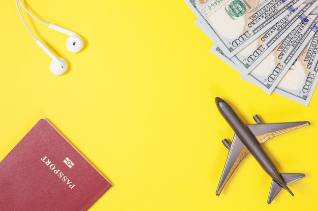 Dollars, airplane, headphones, foreign passport on yellow background. copy space.