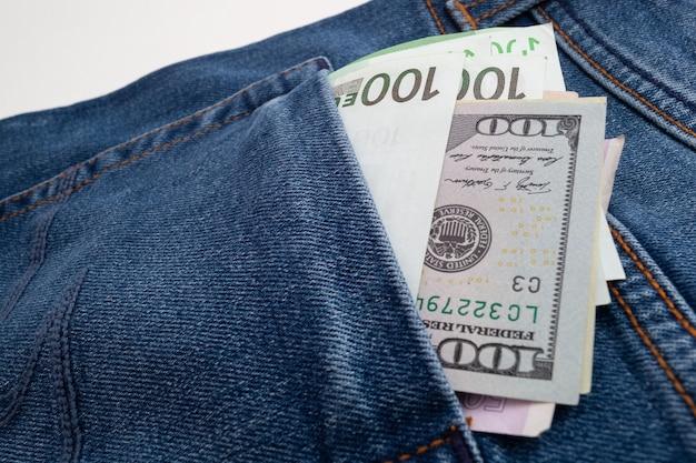 ジーンズのポケットから突き出ているドルとユーロ