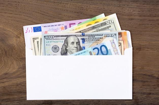 나무 배경에 흰색 봉투에 달러와 유로. 고해상도 사진입니다.