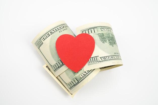 Доллары и сердце, на изолированном белом фоне.