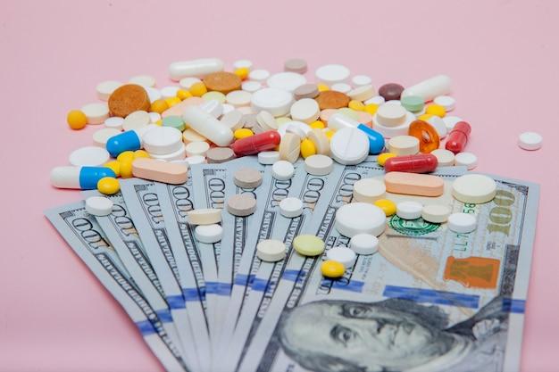 Доллары и таблетки на розовом