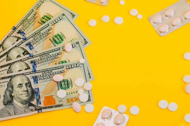 Доллары и таблетки на желтом фоне заделывают. место для текста