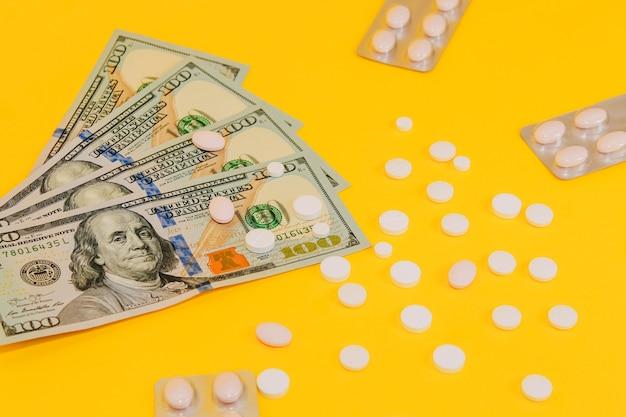Доллары и разбросанные таблетки на желтом фоне крупным планом