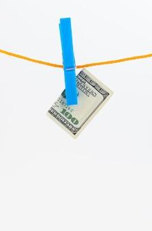 Долларовые банкноты, прикрепленные прищепками к веревке на белом изолированном фоне