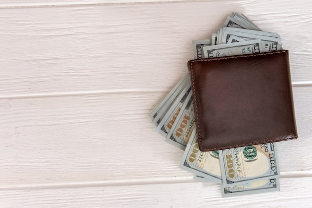 Dollars banknotes in a dark leather wallet,  financial background
