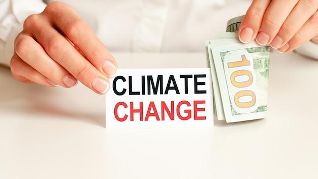달러 빌, 흰색 배경에 흰색 메모장 시트. 기후 변화 텍스트. 금융 및 경제 개념. 금융 개념.