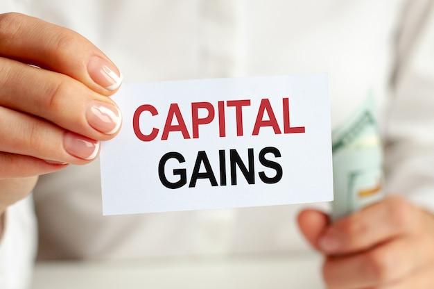ドル札、白い壁に白いメモ帳シート。キャピタルゲインテキスト。金融と経済学の概念。金融の概念。