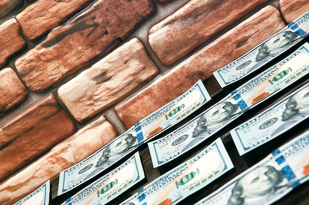 Dollars in bills are spread out on a table near the brick wall