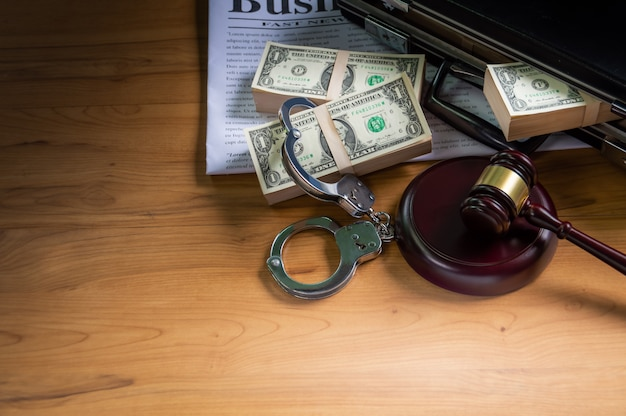 Dollars in briefcase handcuff put on a business newspaper and wooden hammer for a trial.