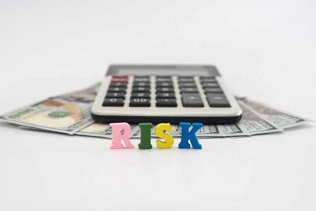 ドル、電卓、そして「リスク」という言葉が白い背景の色付きの文字からレイアウトされています。経済危機、ビジネスリスクの概念。
