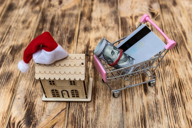 Dollars in cart and house model with santa hat