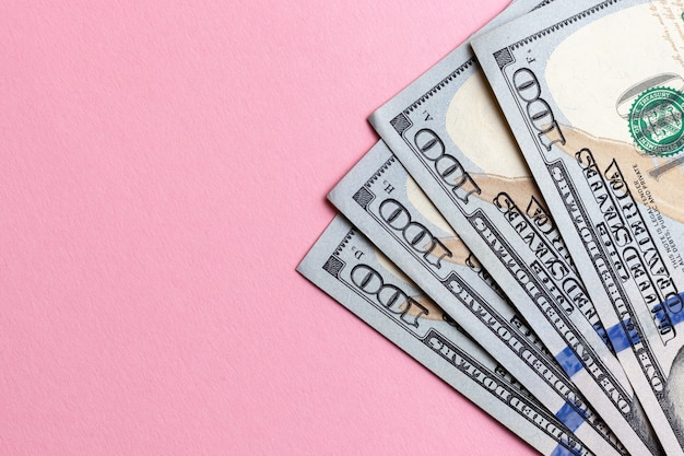 Dollars cash currency at pink background.