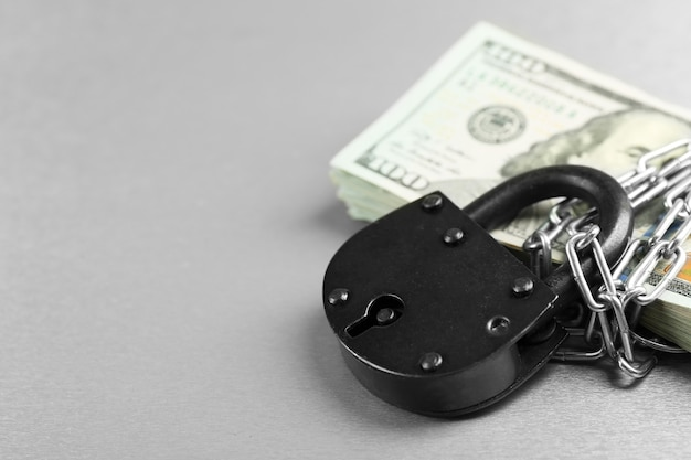 Dollars currency with lock and chain on grey