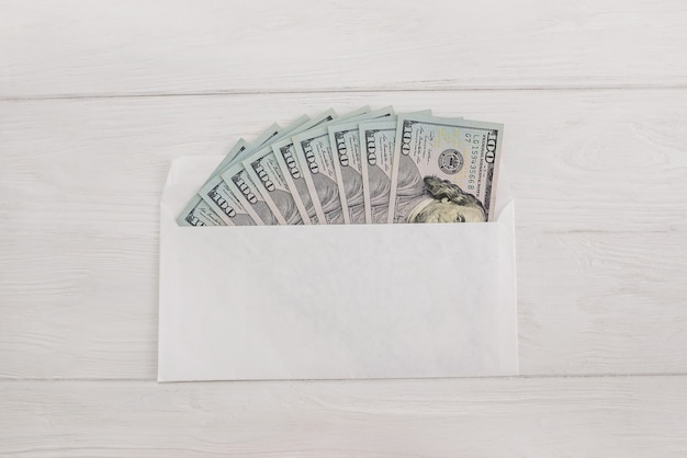 Dollars in an envelope on a white wooden