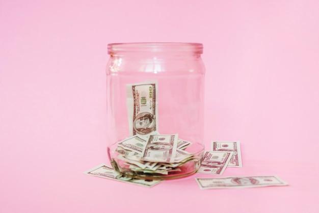 ピンクの背景に瓶の中のドル