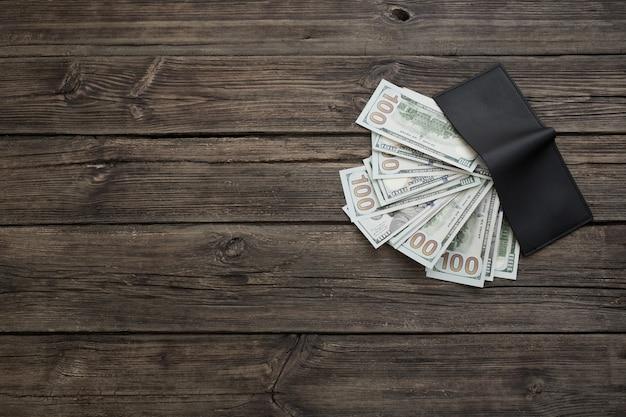 오래 된 나무 배경에 검은 색 지갑에 달러
