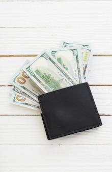 흰색 나무 보드에 검은 색 지갑에 달러