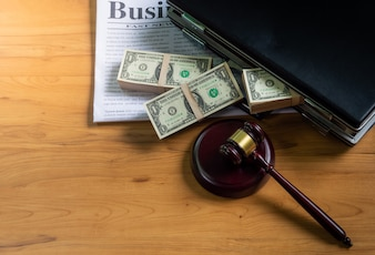 Dollars in briefcase Put on a business newspaper and wooden hammer for a trial concept.