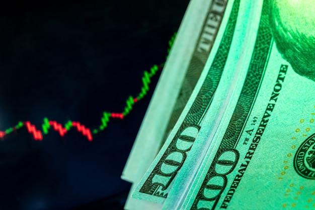 Доллары перед монитором с графиком цен. форекс и торговля. закройте вверх.