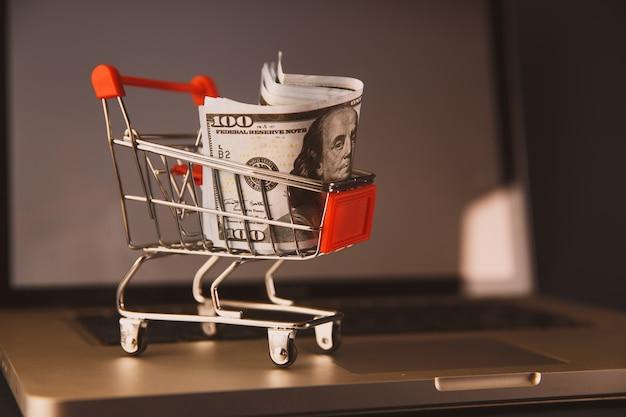 テーブルの上のタブレットとラップトップの背景が付いているバスケットのドルのお金。オンラインビジネス、デジタルマーケティングの概念。