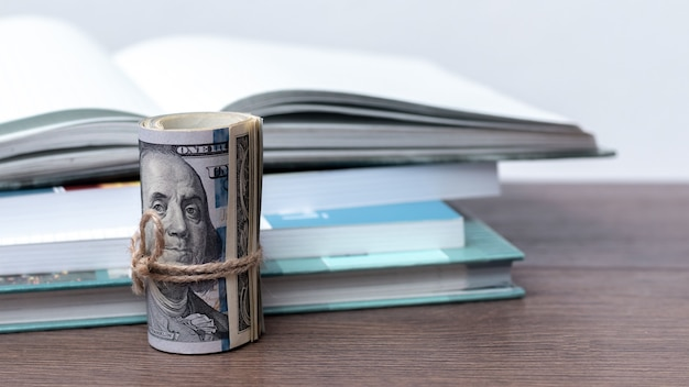Доллары возле стопки книг. плата за обучение. доход от написания книг