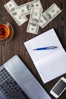 Доллары, блокнот, ручка, смартфон, чай и ноутбук на дереве.
