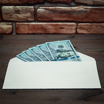 Dollars in onehundreddollar bills are spread out in an envelope on a table near the brick wall