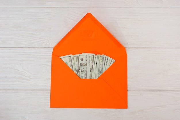 Dollars in an orange envelope on a white wooden background.