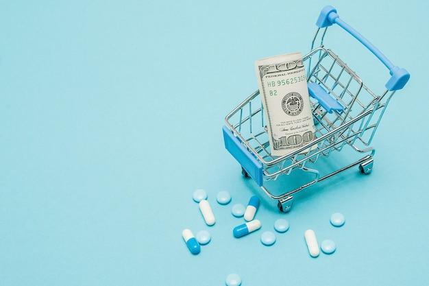 青い背景のドル、丸薬、ショッピングカート。薬局のコンセプト。スペースをコピーします。