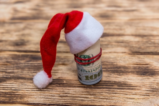 Dollars in roll with santa hat on wooden background