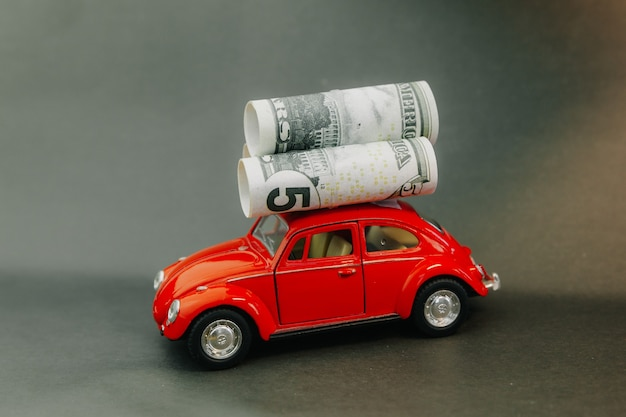 Dollars rolled into a tube on the roof of a miniature model car. red car carrying money
