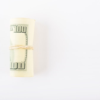 Dollars rolled into tube on white background